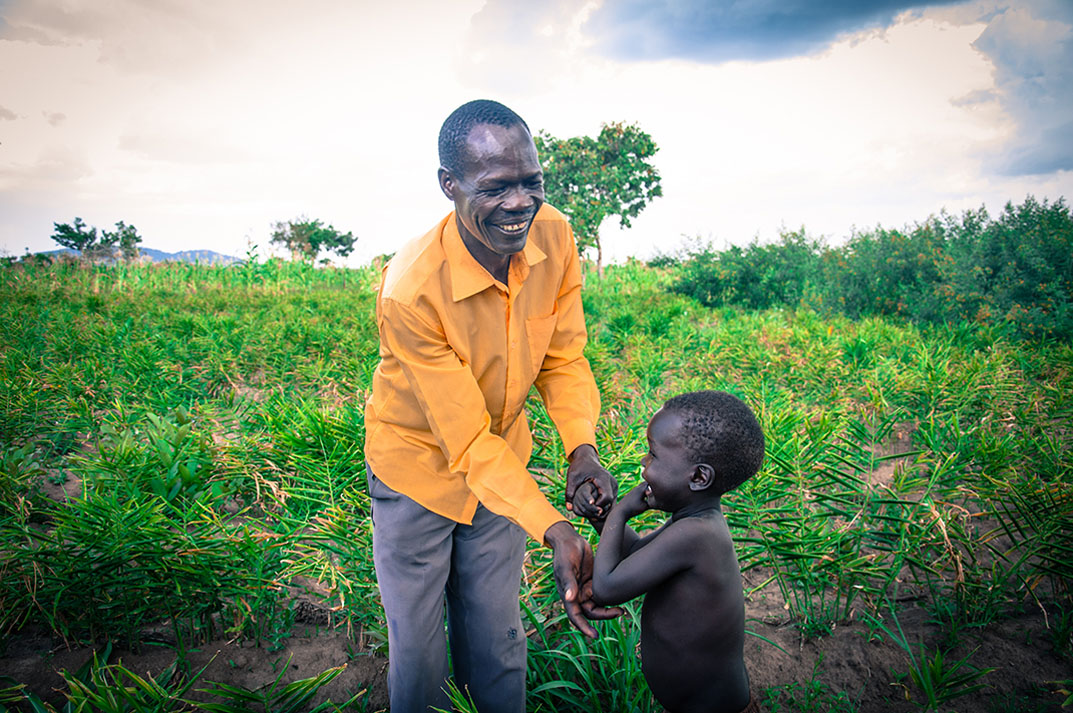 Peter is a farmer in Gulu, in northern Uganda. He is pictured here with his youngest son in his garden of ginger.