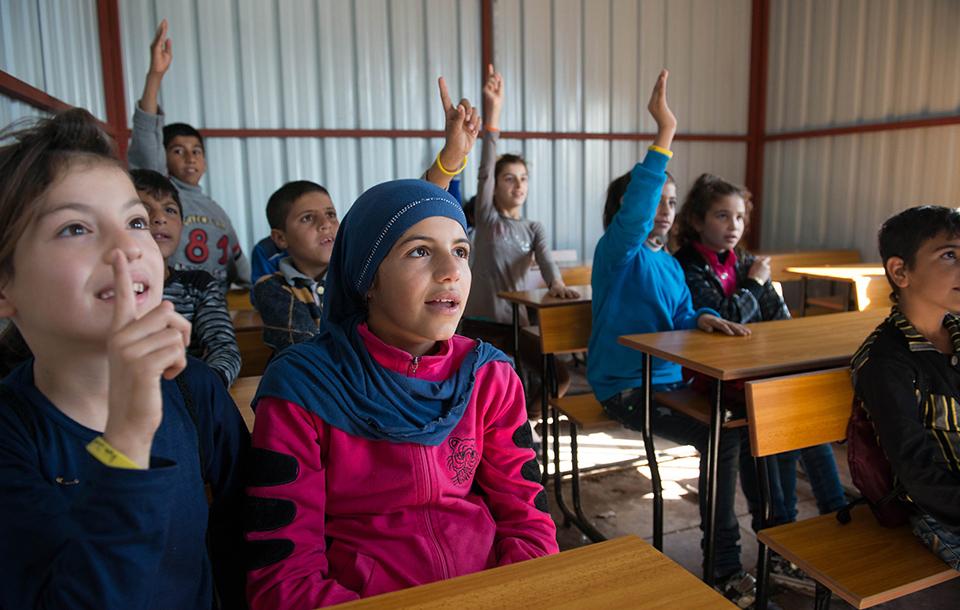 Refugee children sit behind desks during a class in Lebanon.