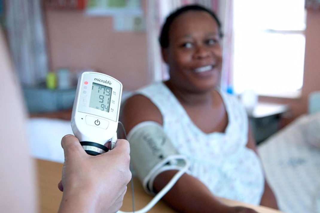 A patient in Haiti has her blood pressure and heart rate checked.
