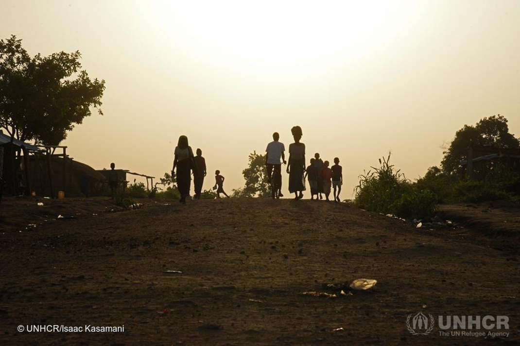 Refugee women and children walk along a dirt track in northern Uganda