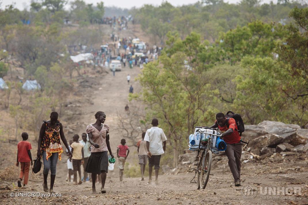 South Sudanese refugees climb a hill at the Bidi Bidi refugee settlement in Uganda.