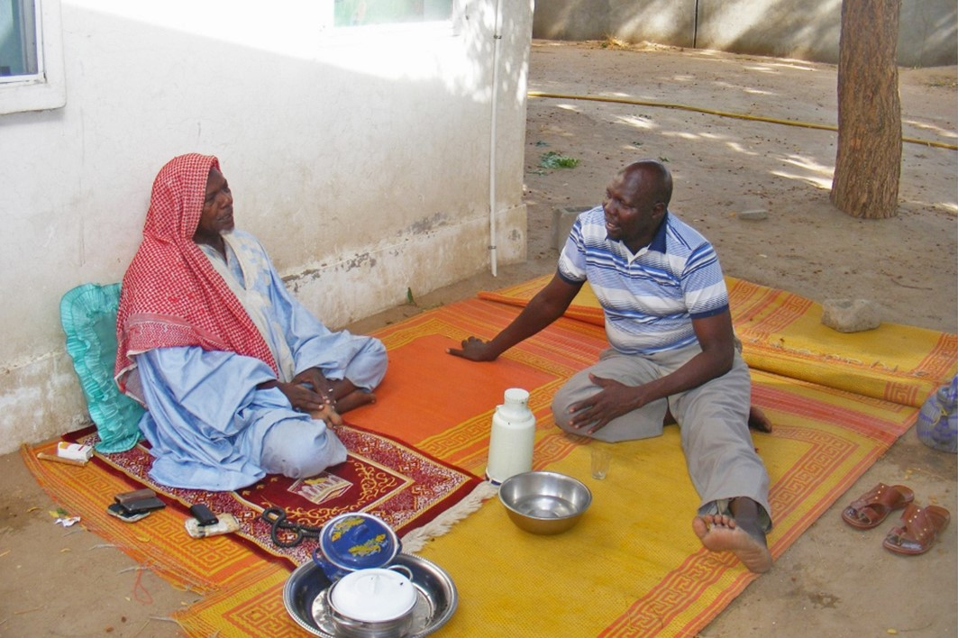 Pastor Djibrine (right) talks to a man at a BMS-supported hospital in Chad.