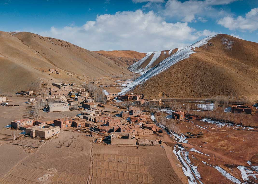 Drone shot of a village in Afghanistan. You can see the snow-capped mountains in the background.