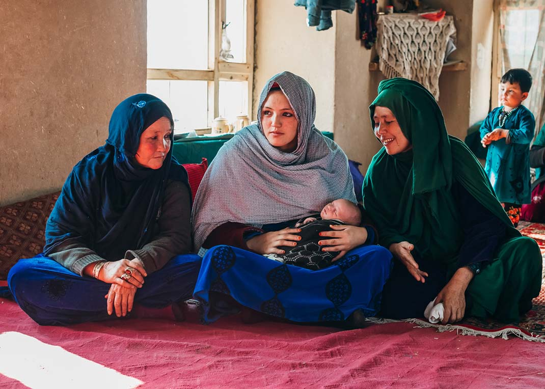 Proud mum and grandmothers watch over 12-day-old Ummed, in their home in a village in Afghanistan's mountains.