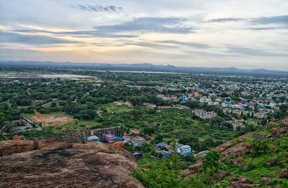A view from high up on a hill of a city in India, with homes and many trees in view.