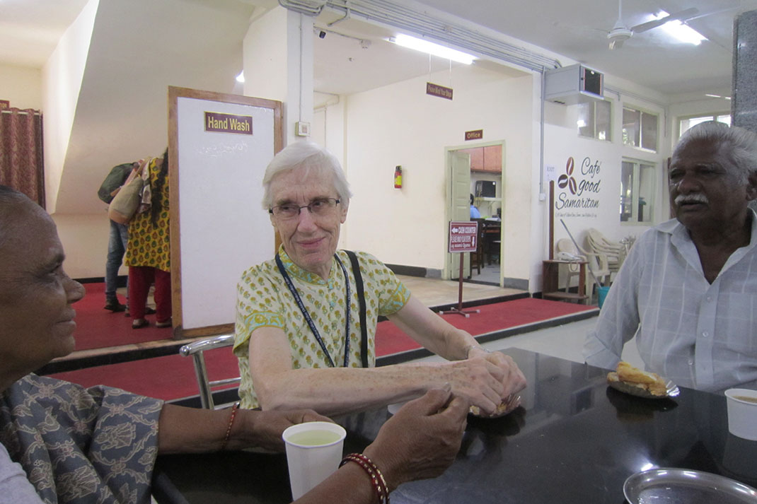 A mature woman with grey hair sits at a table in a hospital cafe with an elderly man on one side, and an elderly woman on another.