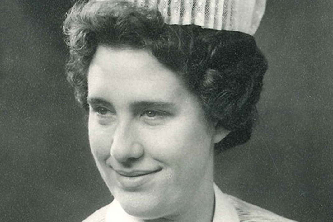 A black and white photo of Ann Bothamley smiling in her nurse's uniform