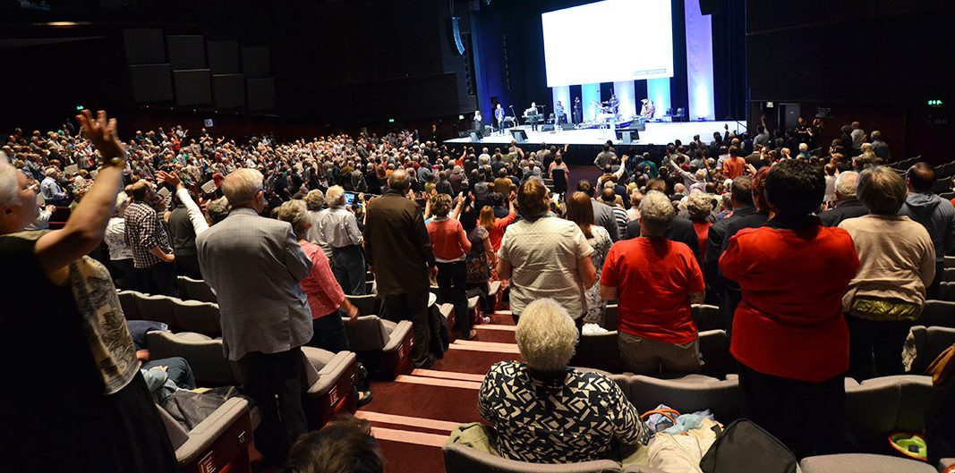 People stand and worship at the Baptist Assembly in 2017