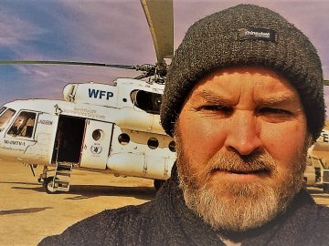 Graeme Riddell, Team Leader for Mission Personnel, Department for World Mission at BMS World Mission, in front of a helicopter in Afghanistan.