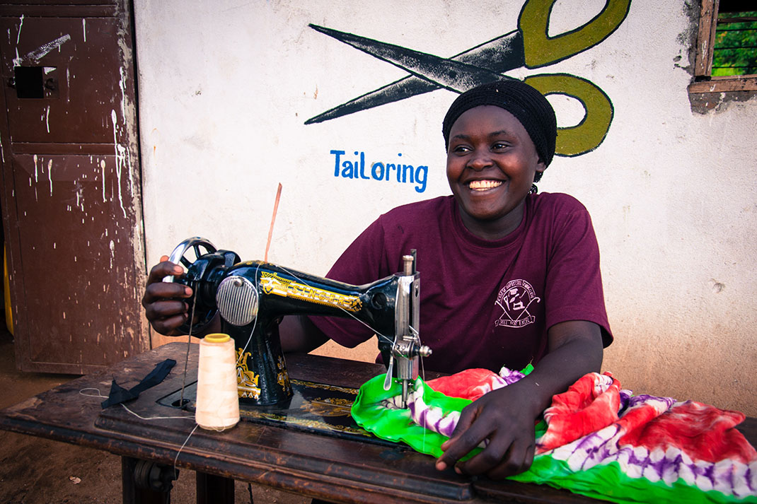 A woman uses a sewing machine at skills centre in Uganda.