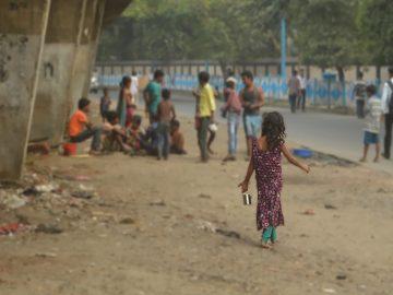 A girl walks towards other children standing under a bridge in India