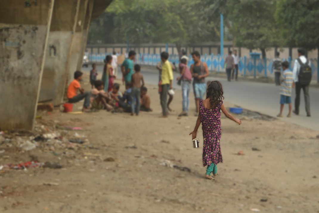 A girl walks towards other children standing under a bridge in India