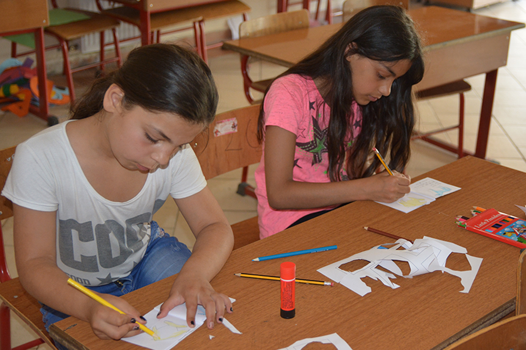 Two girls sit at a table, drawing pictures on pieces of paper