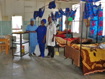 Two female nurses stand next to a male nurse on the children's ward of a hospital