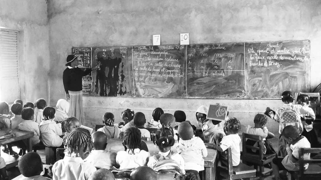 Children sit behind desks as a teacher writes on a chalkboard