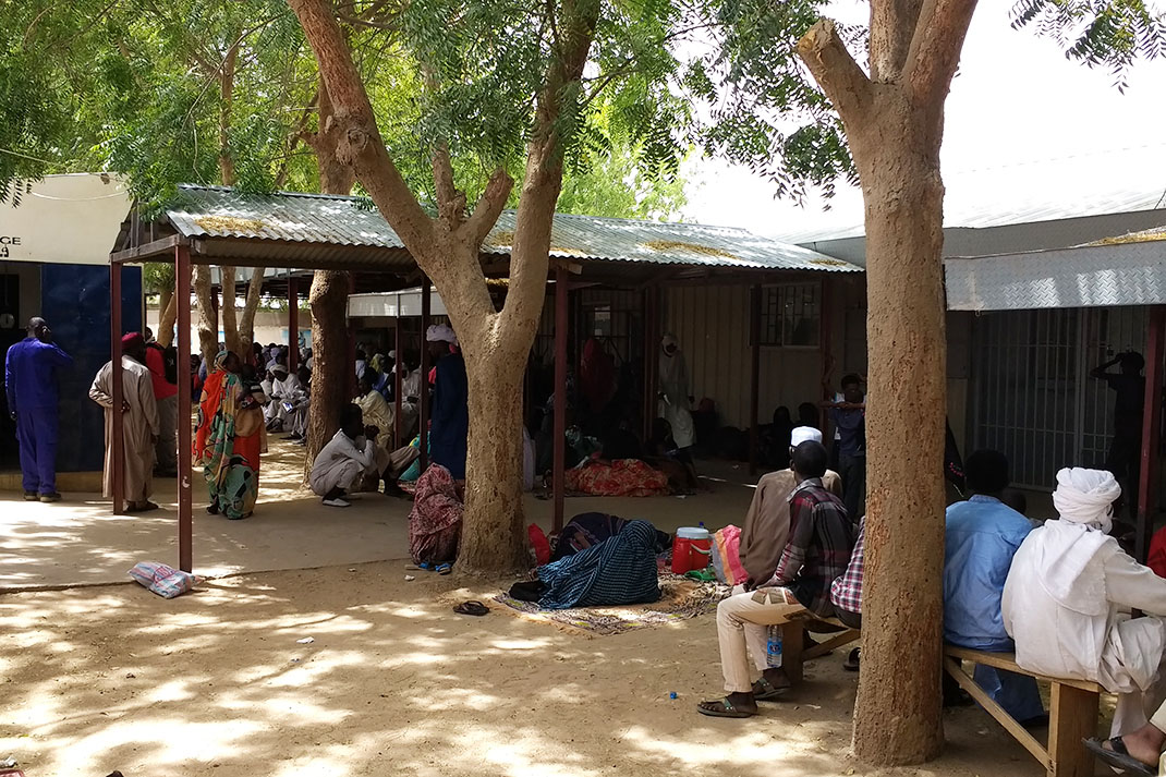Men and woman wait in a shaded area outside a hospital in Chad