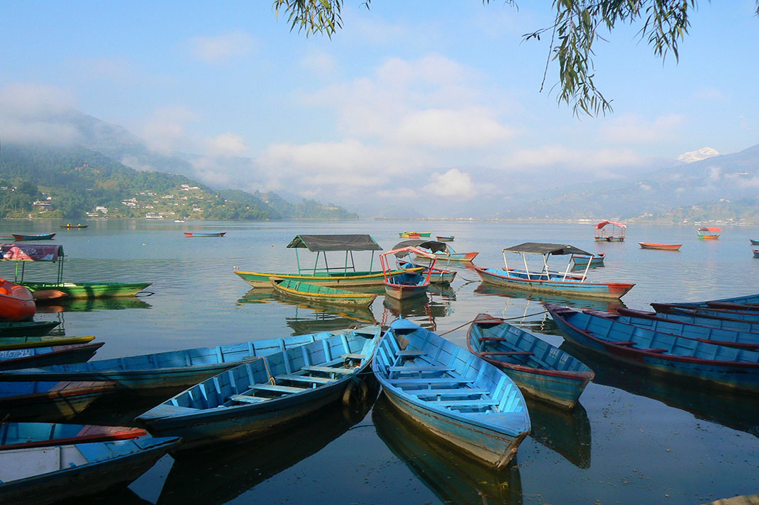 Small blue boats on a lake with mist in the distance