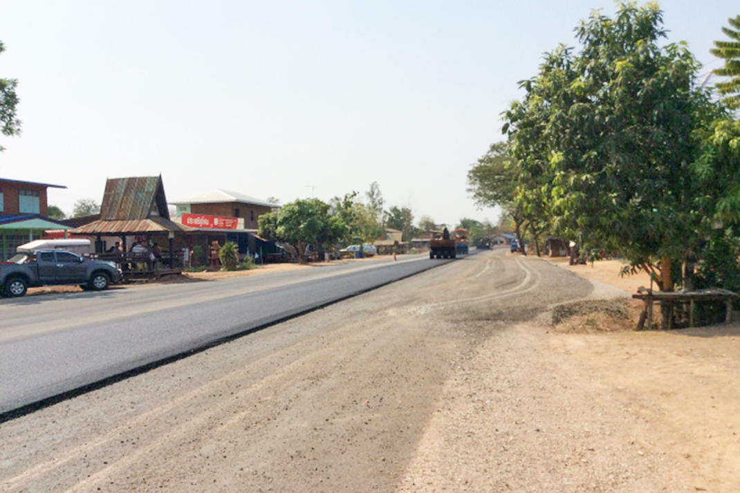 A village road is covered with tarmac. There are shops on one side, and trees on the other.