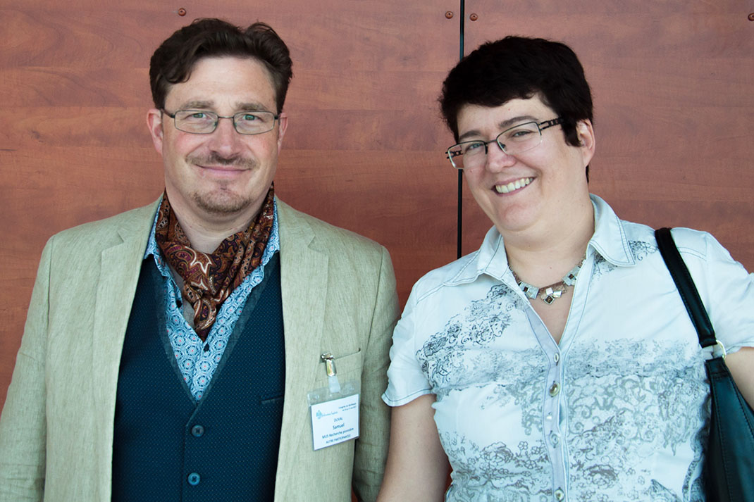 A man wearing glasses and in a jacket and wearing a waistcoat, stands next to a woman with glasses and wearing a light blue shirt