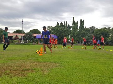 Young football players take the ball round cones on a grass field