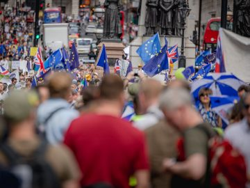Flags of the European Union and Great Britain fly at a rally in London