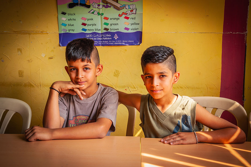 Two Syrian refugee boys sit in a classroom in Lebanon