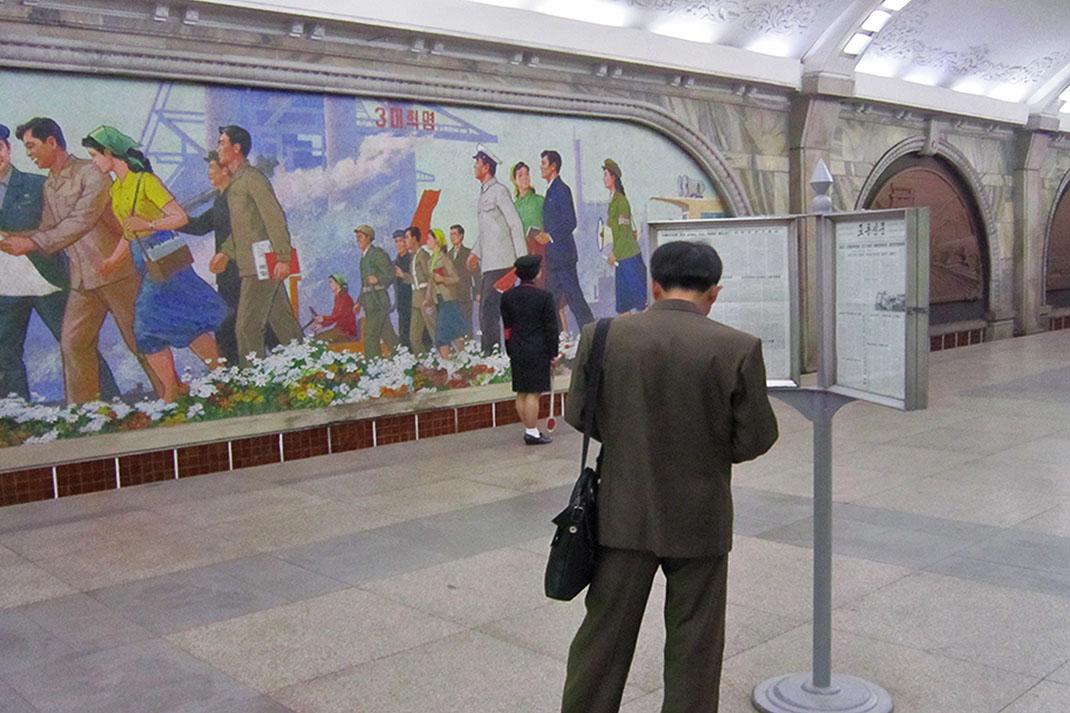 A man reads a newspaper in Pyongyang Metro