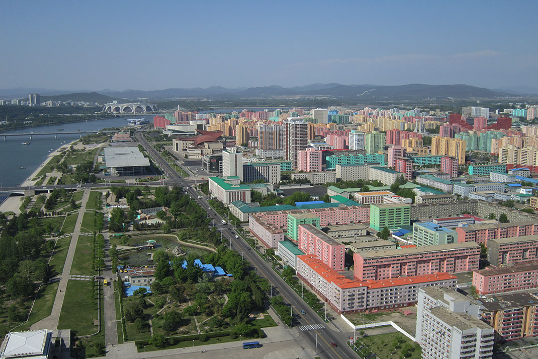Pink and green coloured apartment buildings seen from the top of the Juche Tower in Pyongyang, North Korea