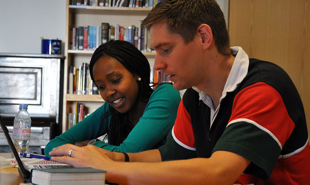 Two trainees work together on a laptop in the library