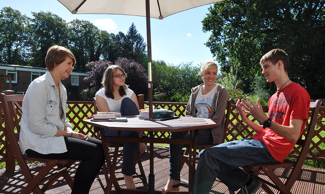 Four trainees chat around a table in the sunny garden at BMS Birmingham