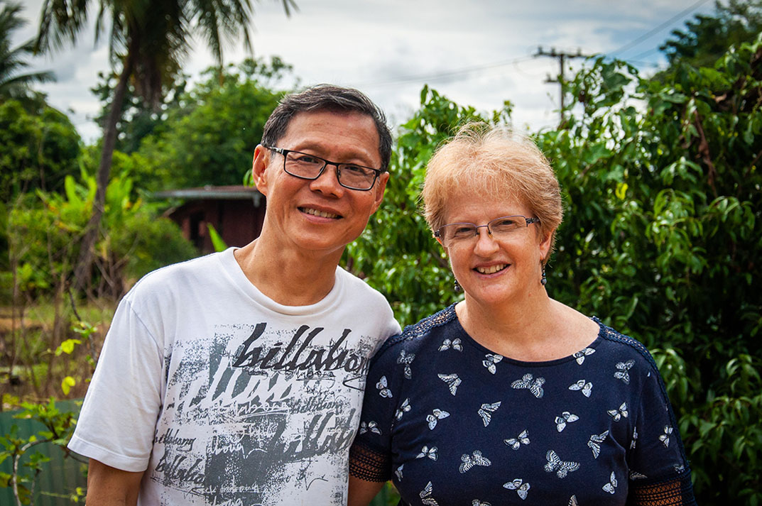 Helen and Wit Boondeekhun stand next to each other in a field in Thailand