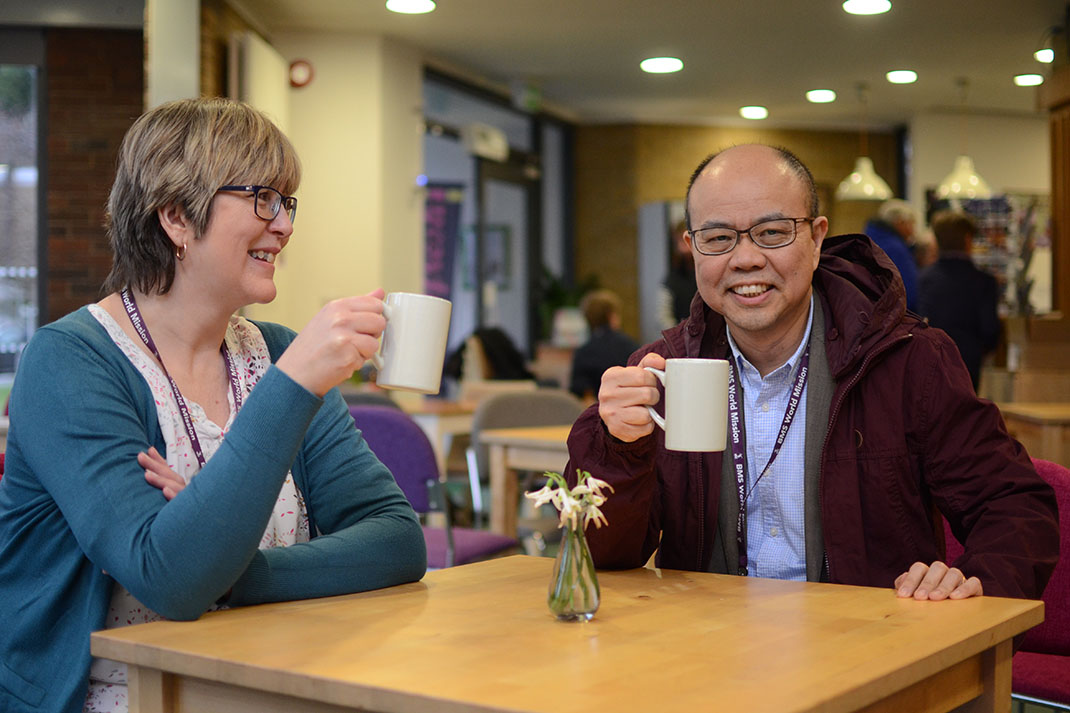 BMS General Director Kang-San Tan holds a cup, along with his colleague, Steph, at a BMS cafe
