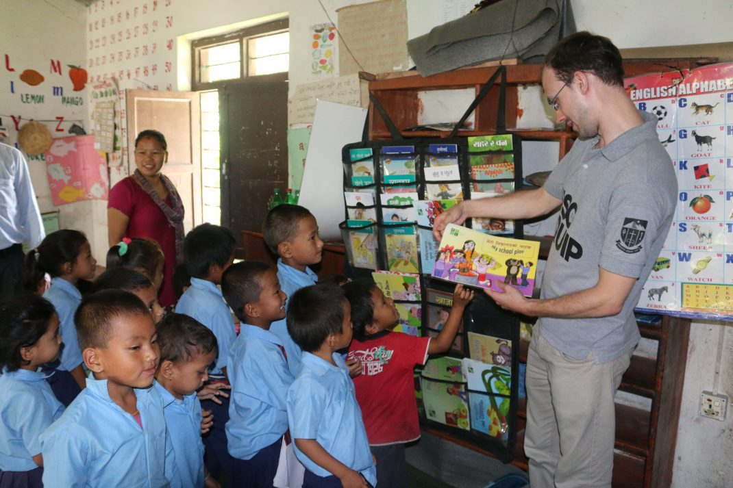 Simon Hall holding a book as children surround him