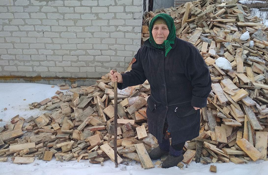 An elderly woman in Ukraine stands by firewood