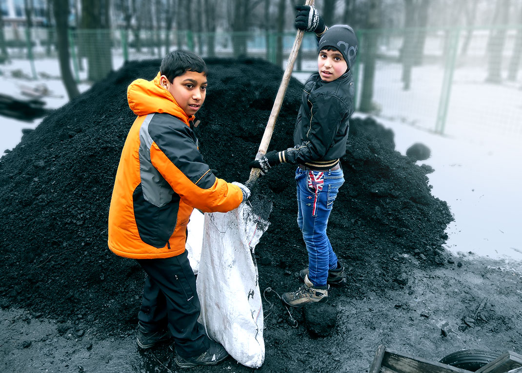Two boys shovel coal into a bag