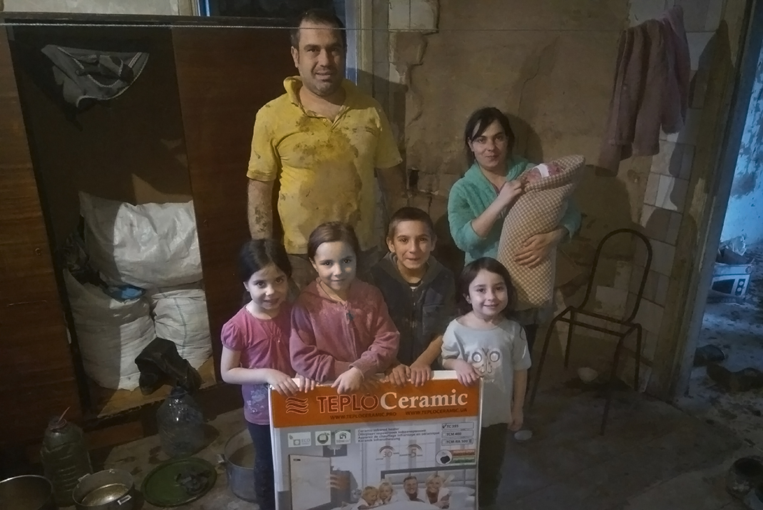 A Ukrainian family in a damaged house, that they escaped to