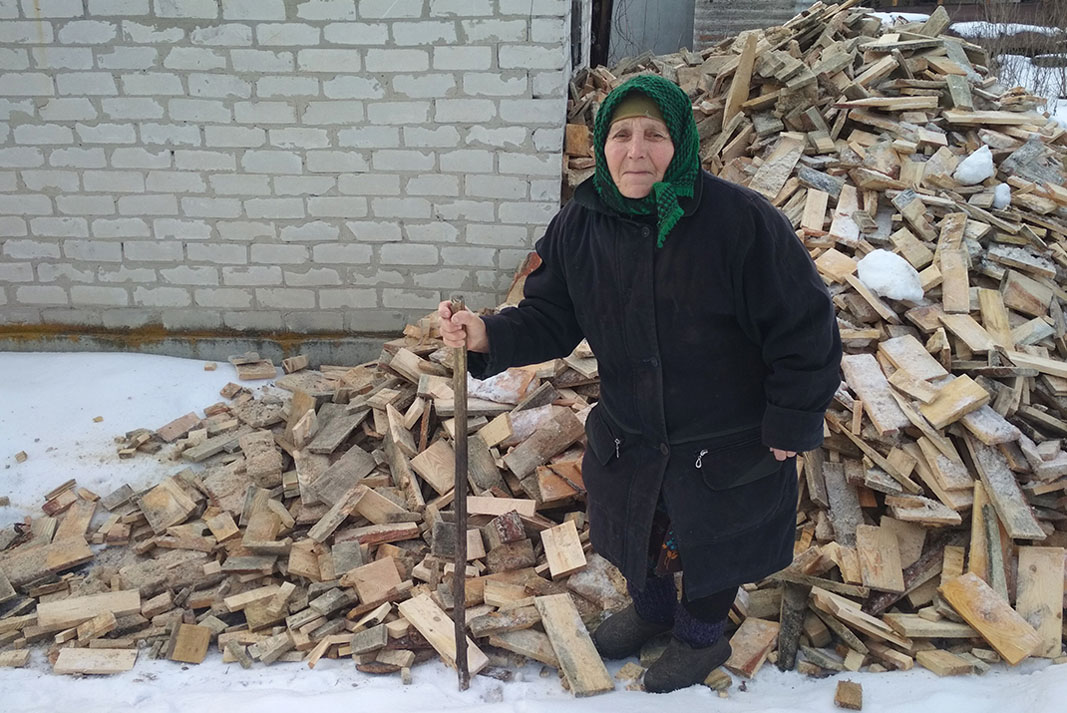 An elderly woman holding a stick stands in front of firewood