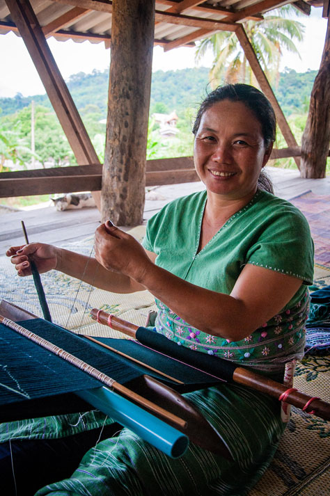A Karen woman sits weaving