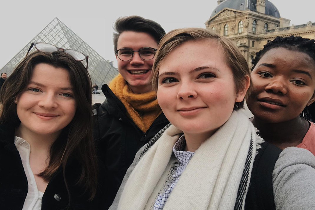 The Action Team in Francetake a selfie in front of the Louvre