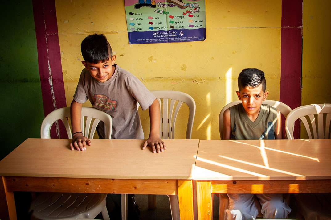 Gabi and Maher sit at the desks in their classroom.