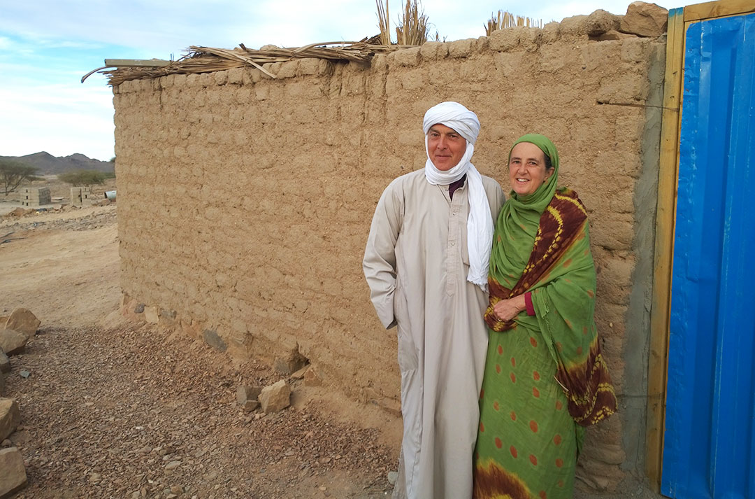 Andrea and Mark Hotchkin in traditional Chadian dress in front of a sand coloured wall