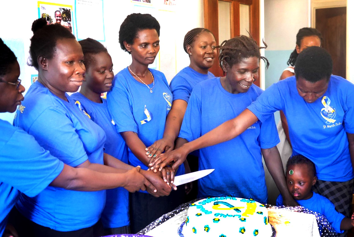 A group of mothers in blue t-shirts stand around a white cake and prepare to cut it.