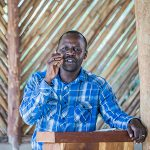 Jimmy Okello preaching to camera in a Ugandan church building