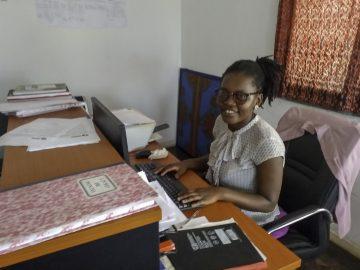 A woman sits behind a desk.