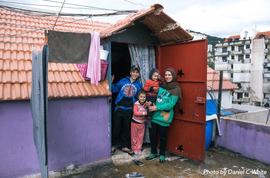 A Syrian family smiling in the doorway of their accommodation