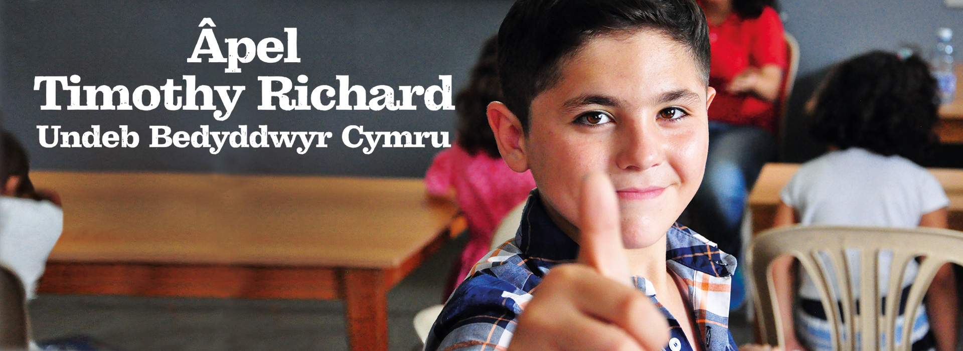 Banner image featuring a boy in a classroom giving the thumbs up and the Welsh title 'Apel Timothy Richard Undeb Bedyddwyr Cymru'