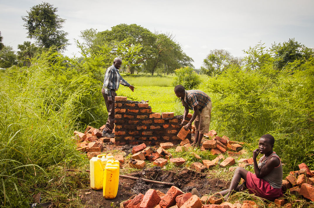 Men building with red bricks