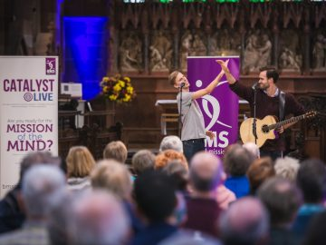 Two men perform in front of a crowd in a church.