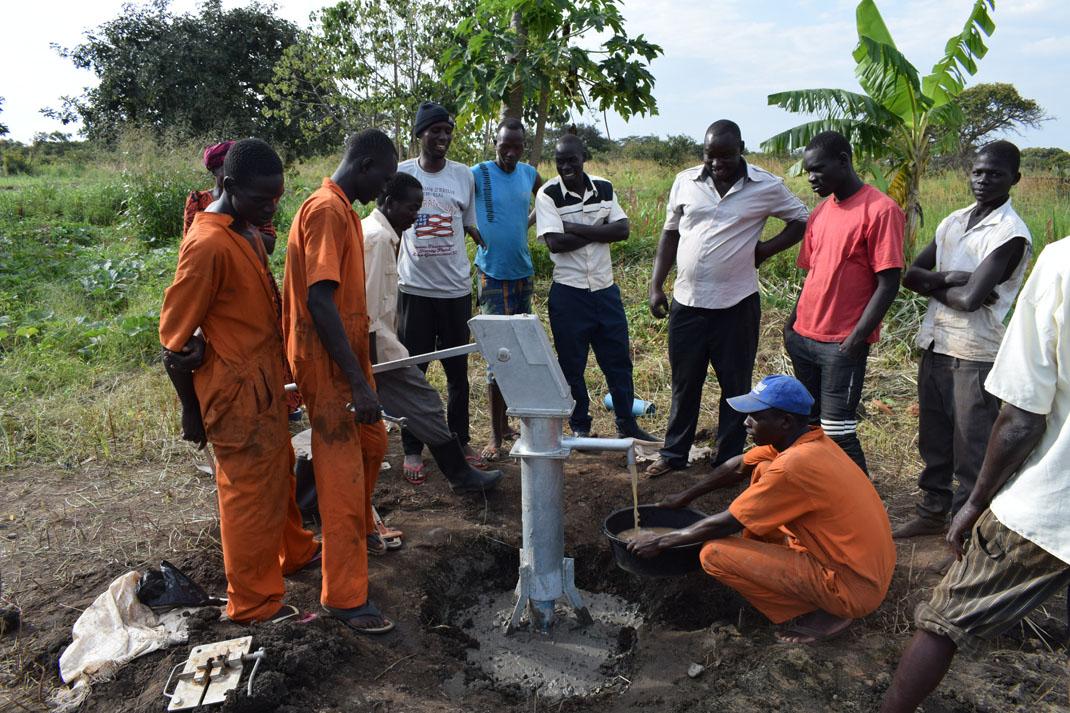 People digging a borehole in Uganda.