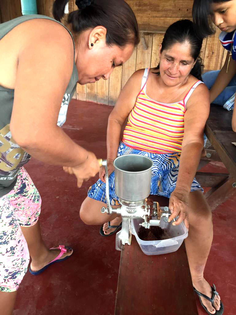 Two Peruvian women grind cocoa beans to make chocolate